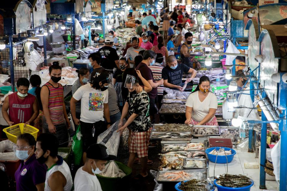 FILE PHOTO: Vendors and customers wearing face masks for protection against the coronavirus disease are seen inside a public market in Quezon City, Metro Manila, Philippines, February 5, 2021. REUTERS/Eloisa Lopez