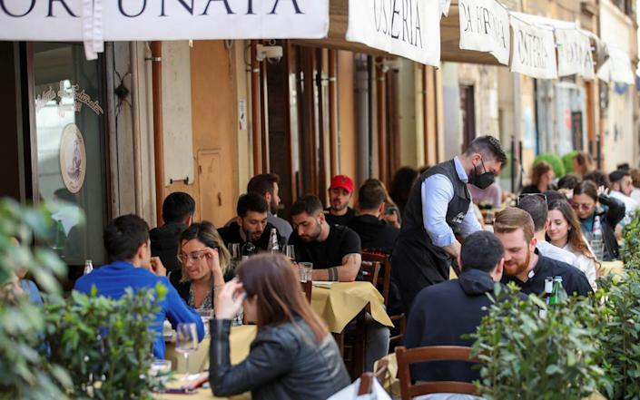 People sit down for lunch at a restaurant in Rome, Italy, as much of the country becomes a 'yellow zone' - YARA NARDI/REUTERS