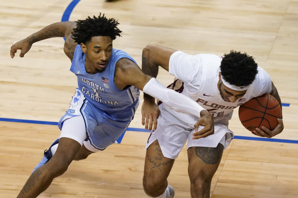 North Carolina guard Leaky Black (1) scrambles for the ball along with Florida State guard Anthony Polite (2) during the second half of an NCAA college basketball game in the semifinal round of the Atlantic Coast Conference tournament in Greensboro, N.C., Friday, March 12, 2021. (AP Photo/Gerry Broome)