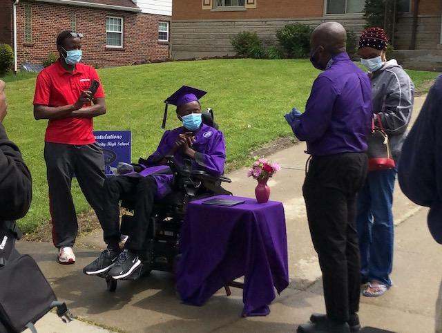 Davenport presents a student with his diploma in front of his home in Cincinnati (Photo: Ramone Davenport)