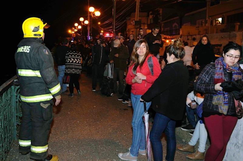 People gather in the street after a strong quake was felt in Valparaiso, northern Chile, late on September 16, 2015 (AFP Photo/Raul Zamora)