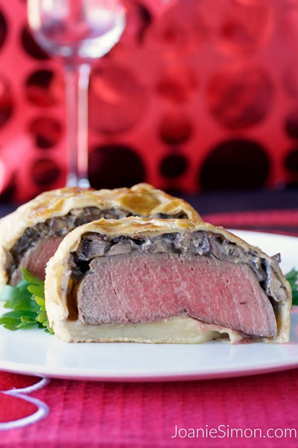 """<p>Puff pastry covers filet mignon and a thin layer of mushroom ragout in this elegant meal for two.</p><p><span><strong>Get the recipe at <a href=""""http://joaniesimon.com/beef-wellington-for-two/"""" rel=""""nofollow noopener"""" target=""""_blank"""" data-ylk=""""slk:Joanie Simon"""" class=""""link rapid-noclick-resp"""">Joanie Simon</a>.</strong></span></p>"""
