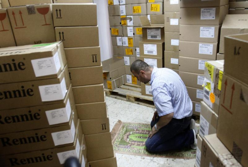 In this Thursday Aug. 16, 2012 photograph, a worker at an Palestinian drug import company prays at the company's warehouse in the West Bank city of Ramallah. The cash crunch, mainly due to a sharp drop in foreign aid since 2011, is threatening to set off a chain reaction of business failures, layoffs and economic downturn that would undermine one of the West's fundamental strategies toward resolving the Israeli-Palestinian conflict. (AP Photo/Nasser Shiyoukhi)