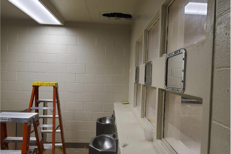 This photo provided Monday, Nov. 4, 2019, by the Monterey County Sheriff's Office shows a hole cut into the ceiling and the area that Santos Fonseca and Jonathan Salazar escaped from in the county jail in Salinas, Calif. The two murder suspects escaped the jail over the weekend after climbing through the hole they made in a bathroom ceiling in their housing unit and then working their way through a wall until they reached a hatch they kicked open to leave the building, an official said Monday, Nov. 4, 2019. (Monterey County Sheriff's Office via AP)