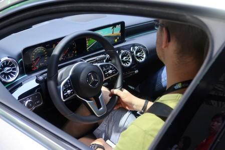 Visitor sits inside a Mercedes Benz vehicle with a car racing game on the screen, at the CES Asia exhibition in Shanghai