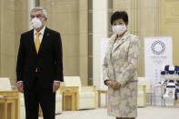 International Olympic Committee President Thomas Bach, left, and Tokyo Governor Yuriko Koike, right, pose for a photo, before their meeting in Tokyo, Monday, Nov. 16, 2020. IOC President Bach is beginning a visit to Tokyo to convince politicians and the Japanese public that the postponed Olympics will open in just over eight months.(AP Photo/Koji Sasahara)