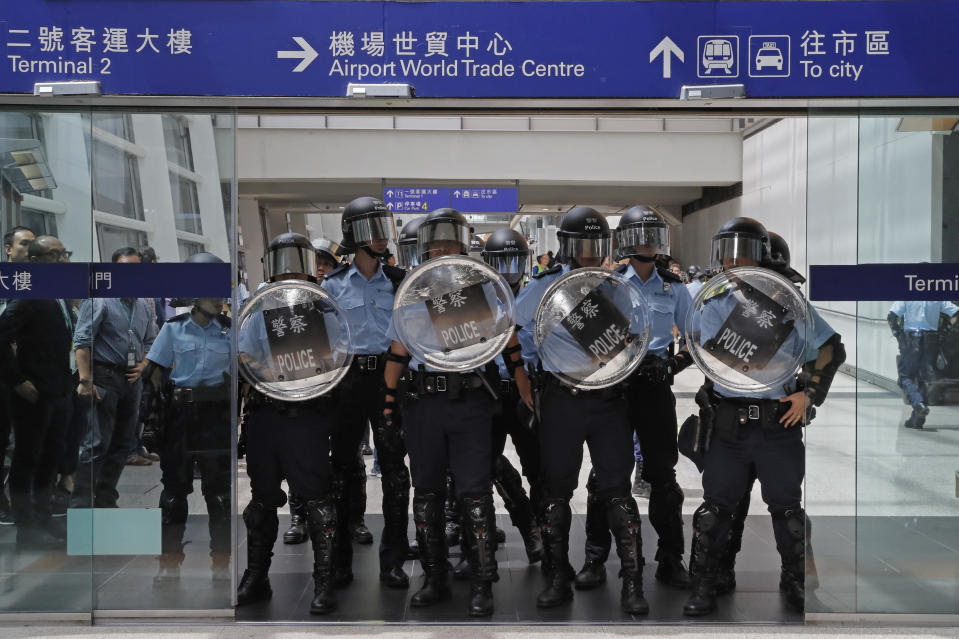 Riot police stand guard at an entrance of the airport in Hong Kong, Sunday, Sept.1, 2019. The operator of the express train to Hong Kong's airport has suspended service as pro-democracy protesters gathered there following a day of violent clashes with police. Protesters gathered at the airport after online calls to disrupt travel. (AP Photo/Kin Cheung)