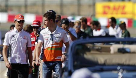 McLaren Formula One driver Jenson Button (L) of Britain and Force India Formula One driver Paul di Resta of Britain walk followed by other drivers during the drivers' parade before the Japanese F1 Grand Prix at the Suzuka circuit October 13, 2013. REUTERS/Issei Kato