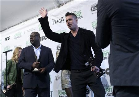 """Producer Brad Pitt (C) waves as he leaves the press room with Best Director winner Steve McQueen (L) after they won the Best Feature award for the film """"12 Years a Slave"""" at the 2014 Film Independent Spirit Awards in Santa Monica, California March 1, 2014. REUTERS/Robert Galbraith"""