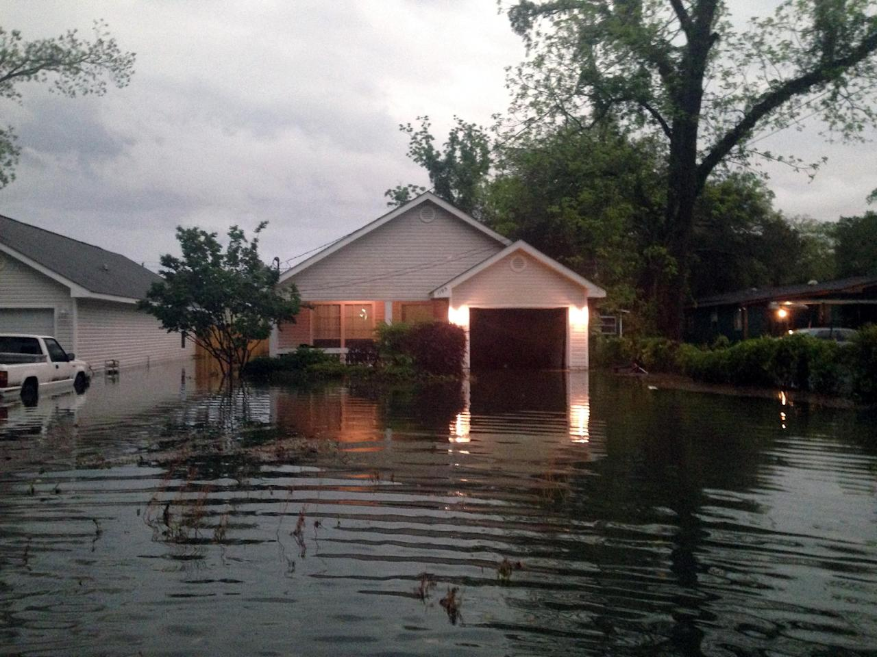 In this photo provided by Kyle Smith, floodwaters surround Smith's home in Pensacola, Fla. on Wednesday, April 30, 2014. Smith had to evacuate his home with his 18-month-old son Tuesday night after severe weather hit the Florida Panhandle, causing widespread flooding. (AP Photo/Kyle Smith)