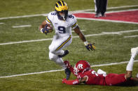 Michigan's Chris Evans (9) avoids a tackle attempt by Rutgers' Tre Avery (21) during the first half of an NCAA college football game Saturday, Nov. 21, 2020, in Piscataway, N.J. (AP Photo/Frank Franklin II)
