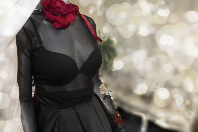 black women's dress detail, With a red flower on her neck