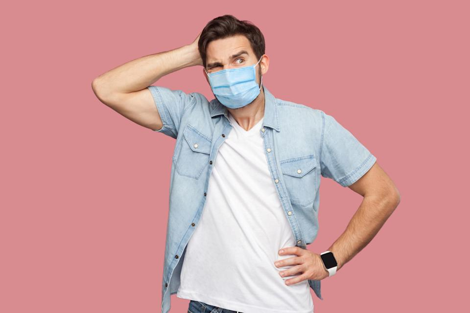 Portrait of young man with surgical medical mask in blue casual style shirt standing, scratching his head, looking away and thinking what to do.