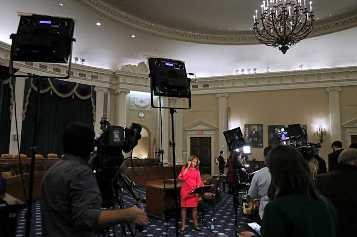 Journalists and camera crews report from inside the hearing room where the House Intelligence Committee will hold its first public impeachment hearing in the Longworth House Office Building on Capitol Hill November 13, 2019 in Washington, DC.