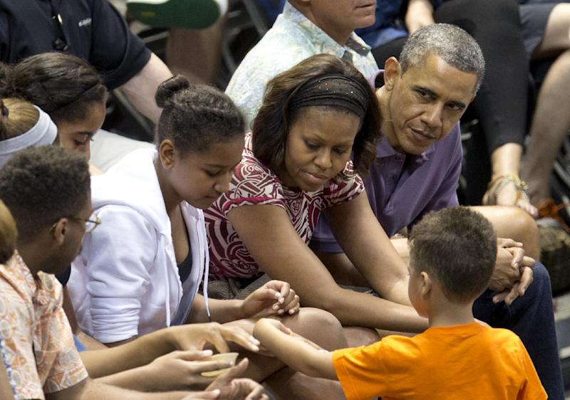 President Barack Obama and first lady Michelle Obama with daughter Sasha, third from right, and Malia, fourth from right sit with family members and friends during the Oregon State University versus University of Akron college basketball game at the Diamond Head Classic at the Stan Sheriff Center in Honolulu, Sunday, Dec. 22, 2013. Michelle Obama's bother, Craig Robinson, is the Coach of Oregon State. The first family is in Hawaii for their annual holiday vacation. (AP Photo/Carolyn Kaster)