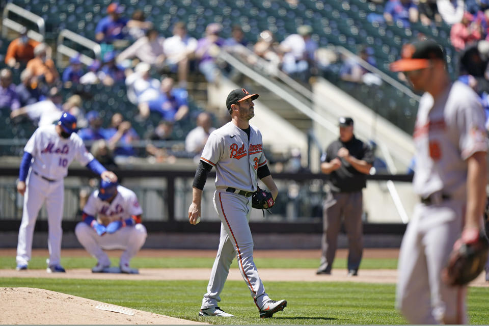 Baltimore Orioles starting pitcher Matt Harvey, center, looks to the outfield with a Mets runner on third during the fifth inning of a baseball game, Wednesday, May 12, 2021, in New York. Harvey allowed seven earned runs in four and a third innings against his former team. (AP Photo/Kathy Willens)