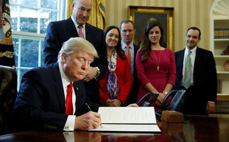 U.S. President Donald Trump signs an executive order rolling back regulations from the 2010 Dodd-Frank law on Wall Street reform at the White House in Washington February 3, 2017.  REUTERS/Kevin Lamarque