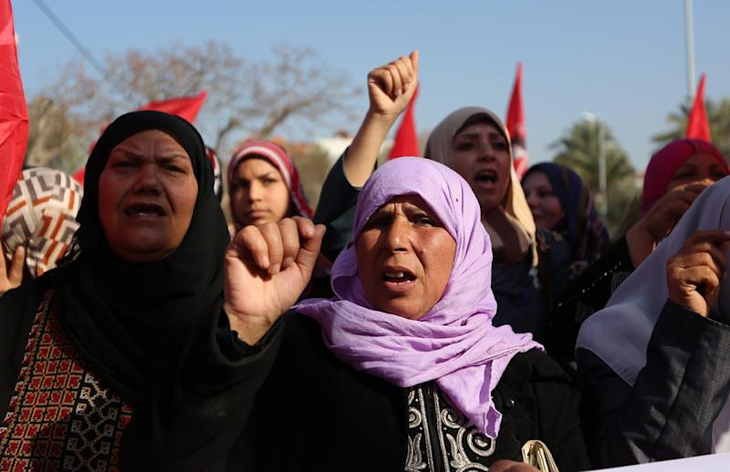 Palestinian women chant slogans and wave Palestinian and red flags, background, that represent the Palestinian Marxist-Leninist secular political and military organization, during a demonstration organized by the Democratic Front for the Liberation of Palestine, against resuming peace talks with Israel in Gaza City, Thursday, Jan. 2, 2014. As U.S. Secretary of State John Kerry returns to the region Thursday, the American message to the Israeli and Palestinian leaders is clear It's time to start making hard decisions , Kerry is bringing his own ideas for the outlines of a peace deal, and early indications are that the plan will include hard-to-swallow choices for both sides. (AP Photo/Hatem Moussa)