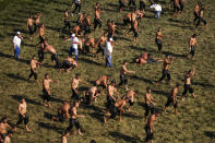 Wrestlers, doused in olive oil, perform the traditional stride on the arena prior to the second day of the 660th instalment of the annual Historic Kirkpinar Oil Wrestling championship, in Edirne, northwestern Turkey, Saturday, July 10, 2021.Thousands of Turkish wrestling fans flocked to the country's Greek border province to watch the championship of the sport that dates to the 14th century, after last year's contest was cancelled due to the coronavirus pandemic. The festival, one of the world's oldest wrestling events, was listed as an intangible cultural heritage event by UNESCO in 2010. (AP Photo/Emrah Gurel)