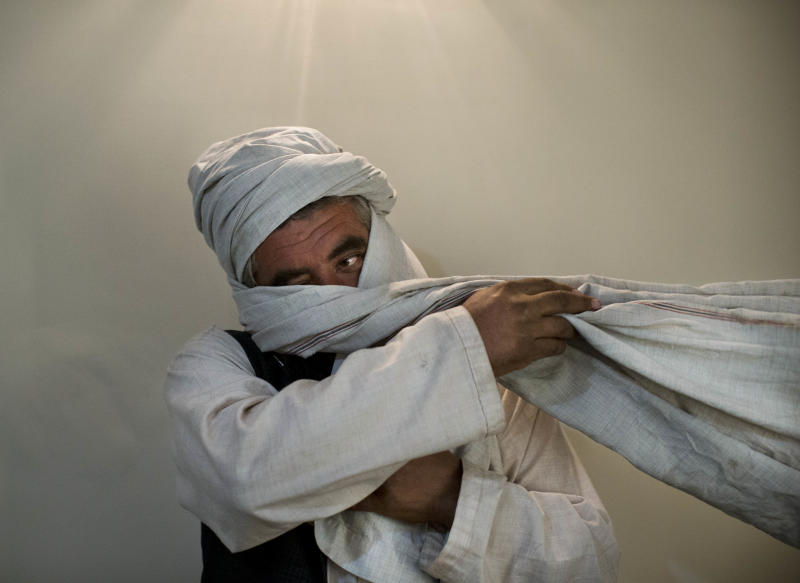 A Monday, Oct. 15, 2012 photo, shows a Taliban fighter from central Afghanistan who is known to the Associated Press from the time of Taliban rule in Afghanistan, but cannot be identified, is seen during an interview with the Associated Press wrapping a cloth around his face, in Kabul, Afghanistan. As the clock ticks toward 2014 and the final withdrawal of NATO and U.S. troops, peace talks with the Taliban are floundering even as the Taliban are showing some hopeful signs, attending international conferences and issuing a statement from their reclusive one-eyed leader with a surprise offer to share power in Afghanistan. (AP Photo/Anja Niedringhaus)