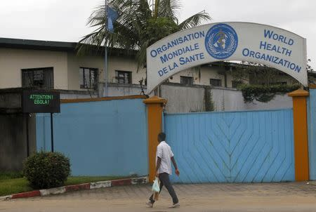 A man walks near a screen displaying a message on Ebola outside the local headquarters of the World Health Organisation (WHO) in Abidjan August 15, 2014. REUTERS/Luc Gnago