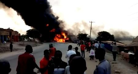 People look towards a fire following a fuel truck collision in Rubirizi