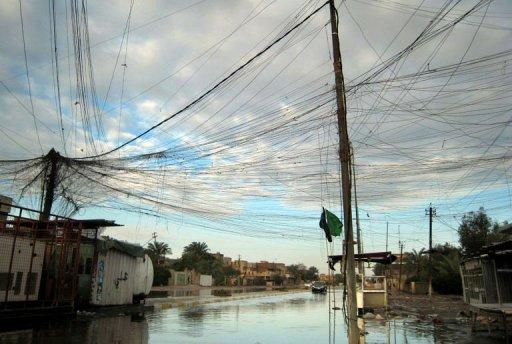 Tangled electrical wires over a flooded street in the Iraqi capital Baghdad on December 26, 2012