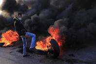 A protester kicks a burning tire to block a highway that links to the Beirut's international airport, in Beirut, Lebanon, Tuesday, March 2, 2021. Scattered protests broke out in different parts of Lebanon Tuesday after the Lebanese pound hit a record low against the dollar on the black market, a sign of the country's multiple crises deepening with no prospects for a new Cabinet in the near future. (AP Photo/Hussein Malla)