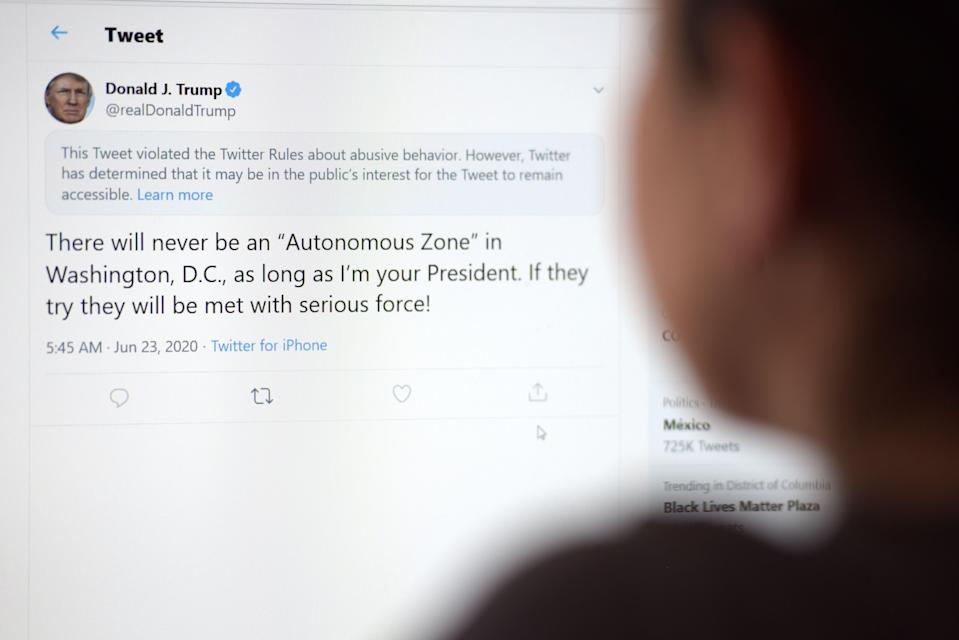 """This illustration photo shows a woman in Los Angeles looking at the official Twitter account of US President Donald Trump on June 23, 2020, with a tweet by the president which Twitter considered """"abusive"""" and hid it. - Twitter on Tuesday hid a tweet from President Donald Trump in which he threatened to use """"serious force"""" against protestors in the US capital, saying it broke rules over abusive content. The move appeared to be the first by Twitter against the president for an """"abusive"""" tweet. In a growing dispute, the platform has recently labeled other Trump tweets as misleading and violating its standards on promoting violence. (Photo by - / AFP) (Photo by -/AFP via Getty Images)"""