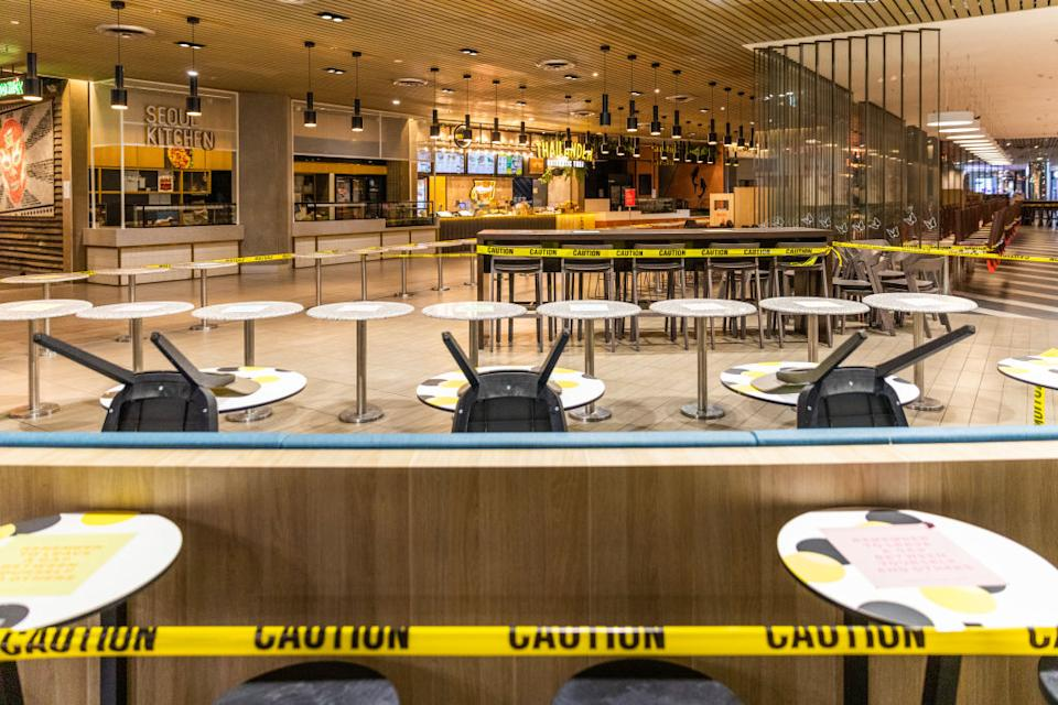 An empty foodcourt with chairs stacked on tables and caution tape around the dining hall in Melbourne. Source: Getty