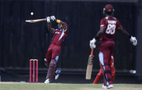 West Indies' Dwayne Bravo plays a shot for four runs of England's Chris Jordan as Darren Sammy looks on during their first one-day international cricket match at the Sir Vivian Richards Cricket Ground in St. John's, Antigua, Friday, Feb. 28, 2014. (AP Photo/Ricardo Mazalan)