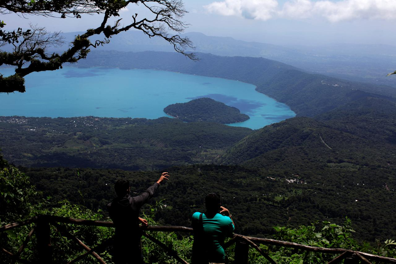 Tourists look at the Coatepeque Lake in El Cerro Verde national park in Izalco, El Salvador August 24, 2016. The color of the water in the Coatepeque lake has changed due to the proliferation of algae species Microcystis aeruginosa and Oscillatoria sp., according to results obtained from an analysis of samples taken on Monday by the Ministry of Environment. REUTERS/Jose Cabezas