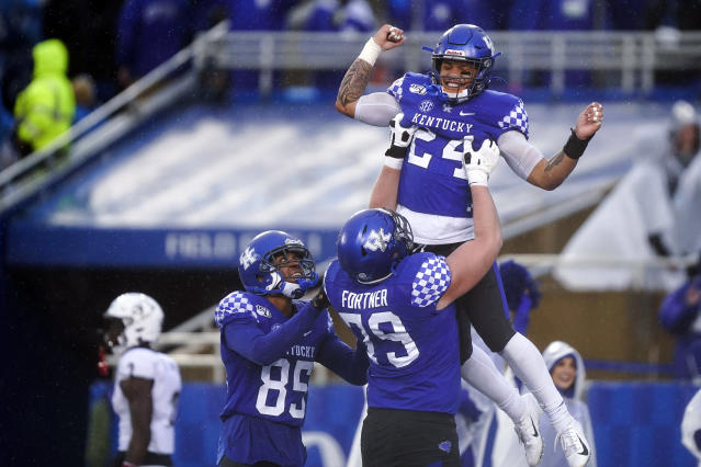 Kentucky running back Christopher Rodriguez Jr. (24) celebrates with offensive tackle Luke Fortner (79) and wide receiver Bryce Oliver (85) after scoring a touchdown during the second half of the NCAA college football game against Louisville, Saturday, Nov. 30, 2019, in Lexington, Ky. (AP Photo/Bryan Woolston)