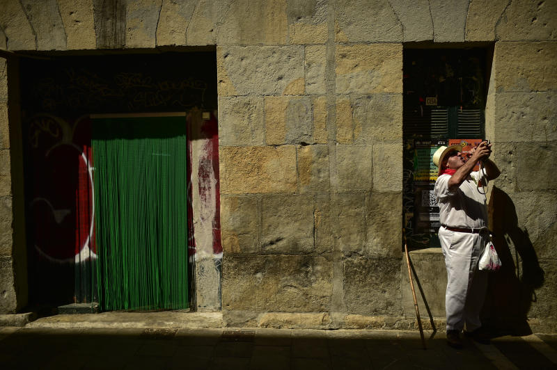A reveler dressed in white and red clothes drinks wine along Estafeta street at the San Fermin Festival, in Pamplona, northern Spain, Wednesday, July 10, 2019. (Photo: Alvaro Barrientos/AP)