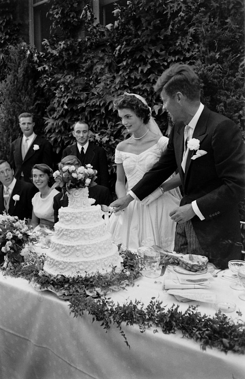 Future US President John F Kennedy (1917 - 1963) and Jacqueline Kennedy (1929 - 1994) (in a Battenburg wedding dress) hold hands as they cut the cake at their wedding reception, Newport, Rhode Island, September 12, 1953. (Photo by Lisa Larsen/Time & Life Pictures/Getty Images)