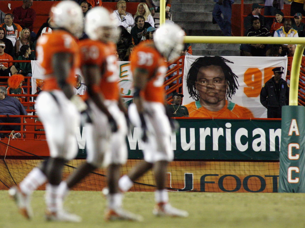 University of Miami Huricanes players walk past a banner of slain teammate Bryan Pata during their NCAA football game against the Boston College Golden Eagles in Miami, Florida, November 23, 2006.  Pata was shot outside his apartment on November 7, 2006.  REUTERS/Marc Serota   (UNITED STATES)
