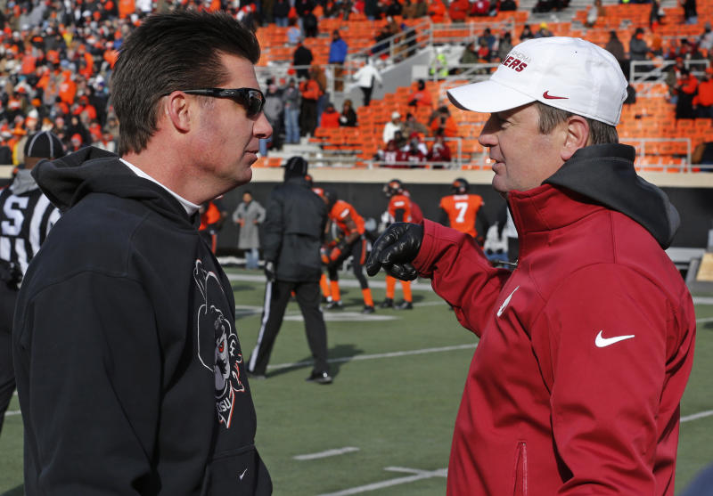 Oklahoma State head coach Mike Gundy, left, and Oklahoma head coach Bob Stoops, right, talk before the start of their NCAA college football game in Stillwater, Okla., Saturday, Dec. 7, 2013. (AP Photo/Sue Ogrocki)