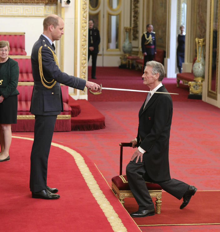 Michael Palin is made a Knight Commander of the Order of St Michael and St George by Prince William during an investiture ceremony at Buckingham Palace, London, Wednesday June 12, 2019. (Yui Mok/PA via AP)