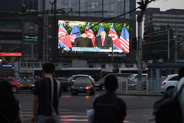 <p>A large outdoor screen shows news footage of the summit meeting in Singapore between President Trump and North Korean leader Kim Jong Un on Tuesday. (Photo: Greg Baker/AFP/Getty Images) </p>
