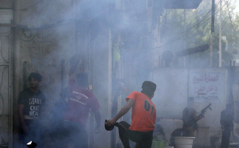 Iraqi riot police fire tear gas to disperse anti-government protesters during ongoing protests in central Baghdad, Iraq, Saturday, Nov. 9, 2019. (AP Photo/Hadi Mizban)