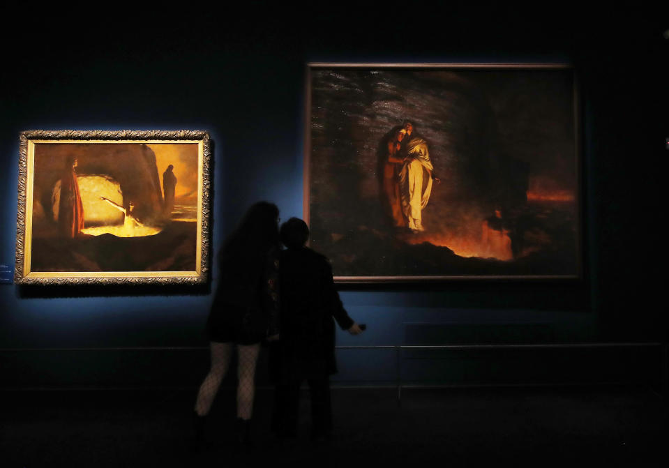 """Women look at """"Dante all'inferno"""" (Dante in hell), 1899 painting, by Camille Boiry, right, and """"Dante incontra Farinata degli Uberti"""", 1900 painting by Silvio Bicchi, at the """"Dante. La visione dell'arte"""" (Dante. The Vision of Art) exhibition, in Forli, Italy, Saturday, May 8, 2021. Italy is honoring its great poet Dante Alighieri in myriad ways on the 700th anniversary of his death, with new musical scores and gala concerts, exhibits and dramatic readings against stunning backgrounds in every corner of the land. (AP Photo/Antonio Calanni)"""
