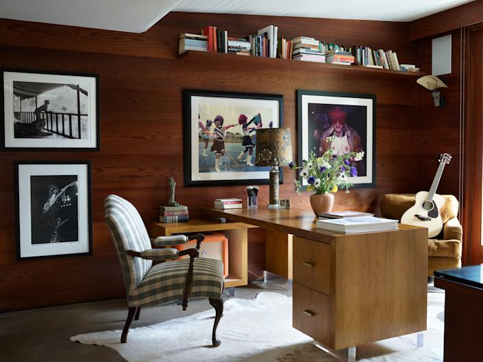 Photographs by Bill Dow and Alice Mann line the wood-paneled office. Antique bergère at vintage desk; vintage cowhide rug.