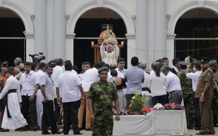 A Sri Lankan Catholic priest raises the statue of St. Anthony during a brief holly mass held outside the exploded church marking the seventh day of the Easter Sunday attacks in Colombo, Sri Lanka, Sunday, April 28, 2019. Sri Lanka's Catholics on Sunday awoke preparing to celebrate Mass in their homes by a televised broadcast as churches across the island shut over fears of militant attacks, a week after the Islamic State-claimed Easter suicide bombings. (AP Photo/Eranga Jayawardena)