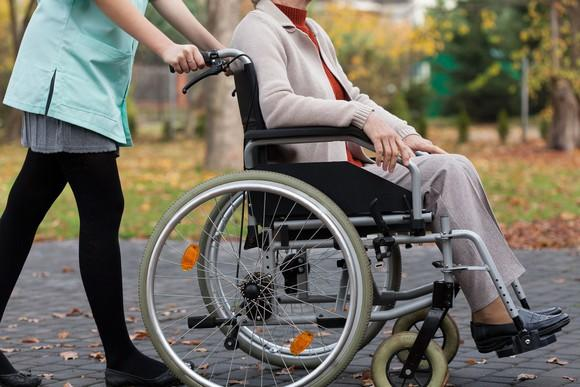 Disabled woman in wheelchair being pushed by caregiver