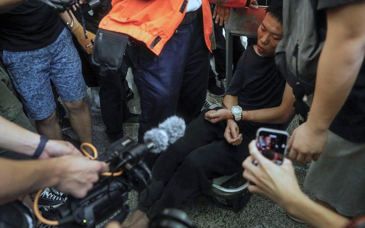 Cameramen and photographers film a detained man, who protesters claimed was a police officer from mainland China - AP