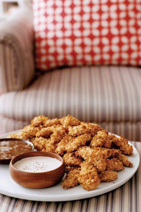 """<p>We've cut the fat from these irresistibly crispy chicken fingers by baking them in the oven instead of deep frying.</p><p><strong><a href=""""https://www.countryliving.com/food-drinks/recipes/a1029/crispy-oven-chicken-fingers-3134/"""" rel=""""nofollow noopener"""" target=""""_blank"""" data-ylk=""""slk:Get the recipe"""" class=""""link rapid-noclick-resp"""">Get the recipe</a>.</strong><br></p>"""