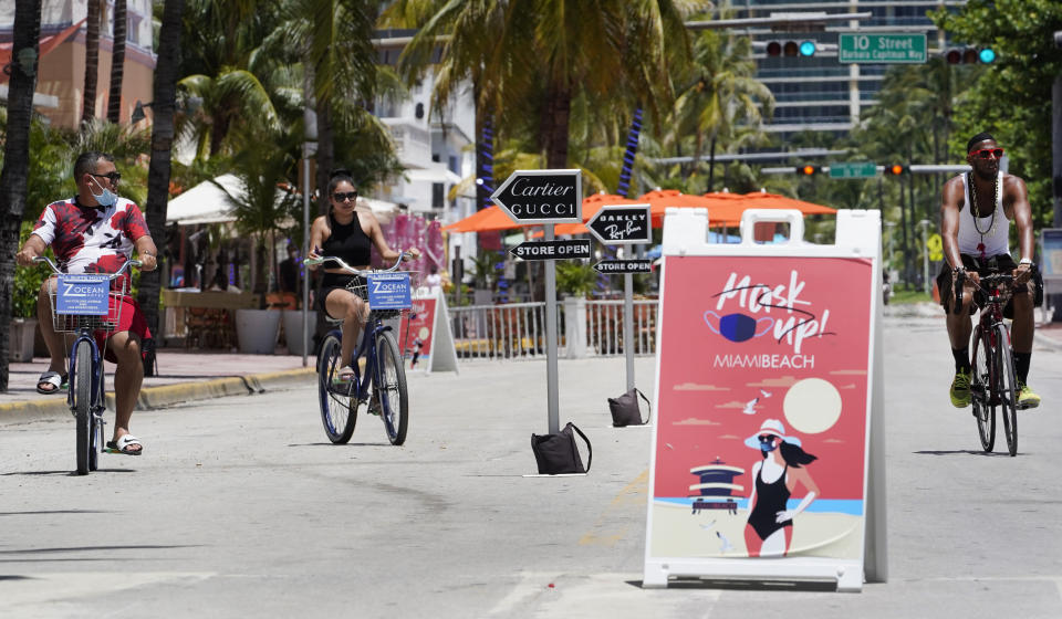 """Bike riders ride past a """"Mask Up Miami Beach,"""" sign, Tuesday, Aug. 11, 2020, in Miami Beach. Florida added at least 276 fatalities to its coronavirus death toll on Tuesday, a new state record. (AP Photo/Wilfredo Lee)"""
