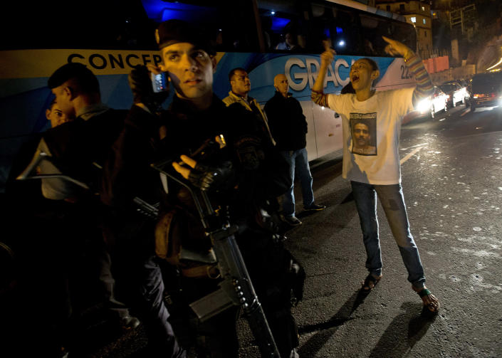"""FILE - In this Aug. 14, 2013 file photo, Elizabeth Gomes, right, shouts at Brazilian policemen during a protest demanding information about her husband Amarildo de Souza, went missing, at the Rocina slum, in Rio de Janeiro, Brazil. Human rights activists and police watchdogs say the case of de Souza, a 42-year-old construction worker who an internal police investigation found was tortured, killed and """"disappeared"""" by officers in July, is emblematic of deeper problems with Rio's plan to clear slums of gangs who have held sway over most of the city's thousand shantytowns for decades. (AP Photo/Silvia Izquierdo, File)"""