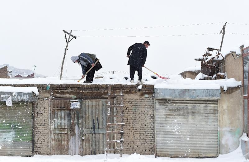 Afghan shopkeepers shovel snow from the roof of their shop during snowfall in Kabul on February 5, 2017 (AFP Photo/WAKIL KOHSAR)
