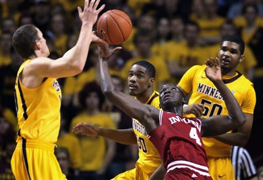 Indiana's Victor Oladipo (4) attempts to grab a loose ball while surrounded by Minnesota's Oto Osenieks, left, Andre Ingram, center back, and Ralph Sampson III, right, during the first half of an NCAA college basketball game on Sunday, Feb. 26, 2012, in Minneapolis. (AP Photo/Tom Olmscheid)